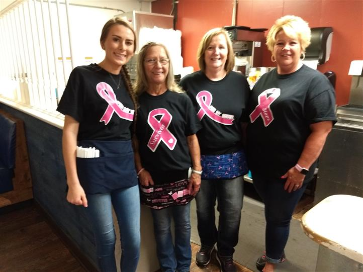 Four women standing smiling for a photo wearing matching black t-shirts with pink bows
