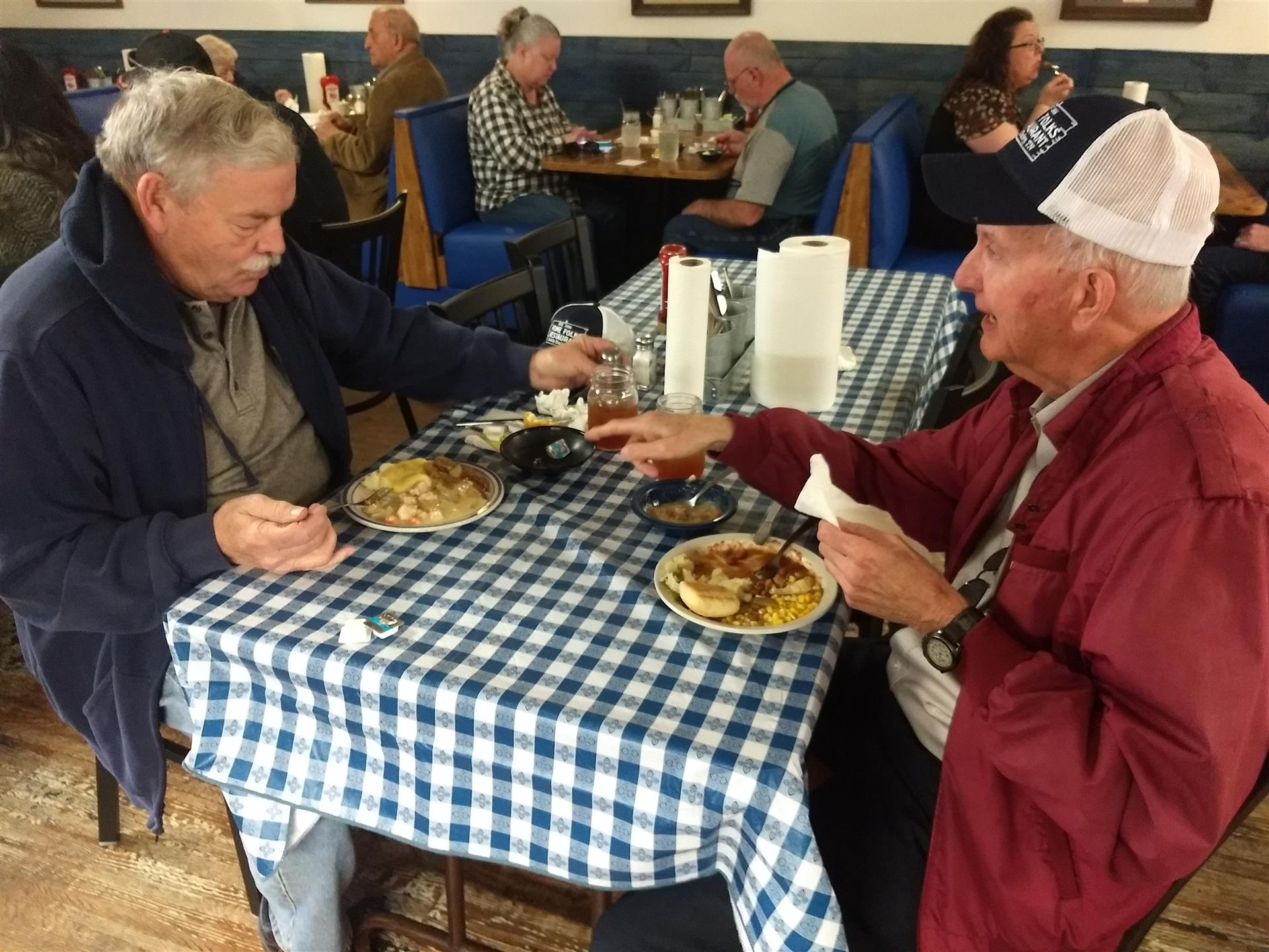 2 older gentlemen sitting at a table in the restaurant with plates of food