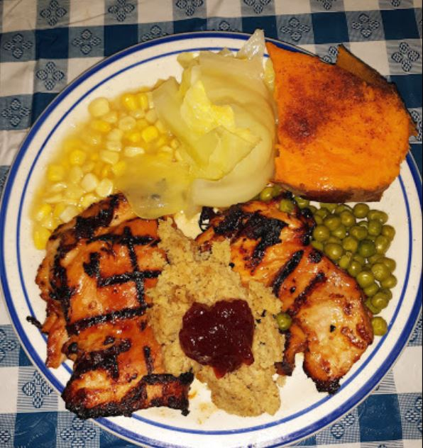 grilled chicken on a plate with cranberry sausage, stuffing, peas, corn, mashed potaotes and a sweet potato