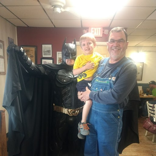 rick standing with batman and holding a child
