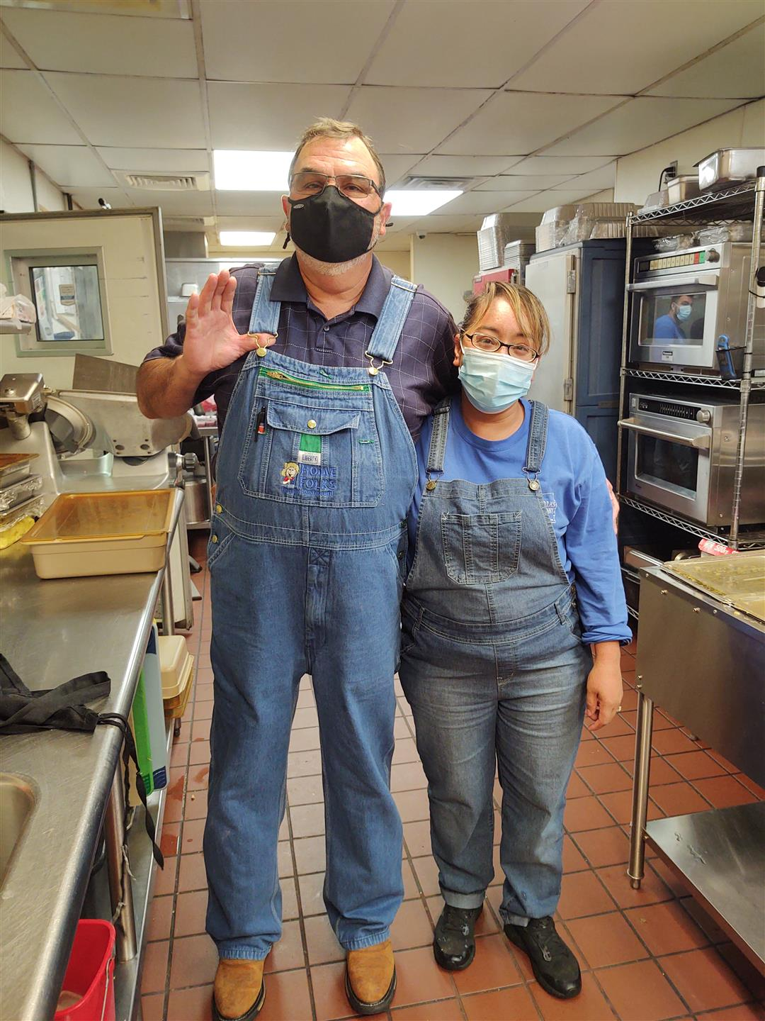 Rick and employee standing in kitchen with masks on