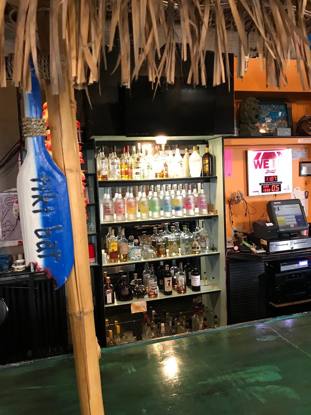 view of bar with wood paneling behind register, and lit shelves with assorted bottles of liquor