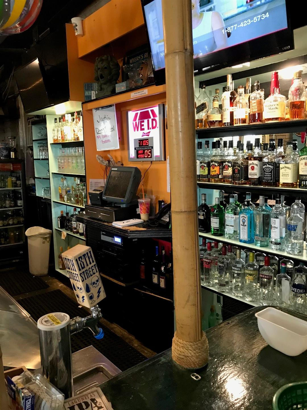 view of bar with wood paneling behind register, and shelves with assorted bottles of liquor