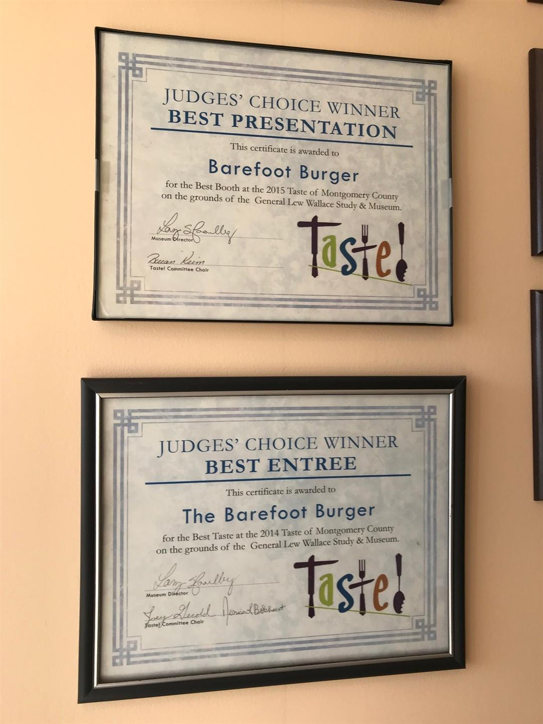 """2 Signs that say """"Judge's Choice Wnner- Best Entree: The Barefoot Burger."""" One Says: """"for the Best Taste at the 2014 Taste of Montgomery County on the grounds of the General Lew Wallace Study & Museum."""" & The other says: for the Best Booth at the 2015 Taste of Montgomery County on the grounds of the General Lew Wallace Study & Museum."""""""
