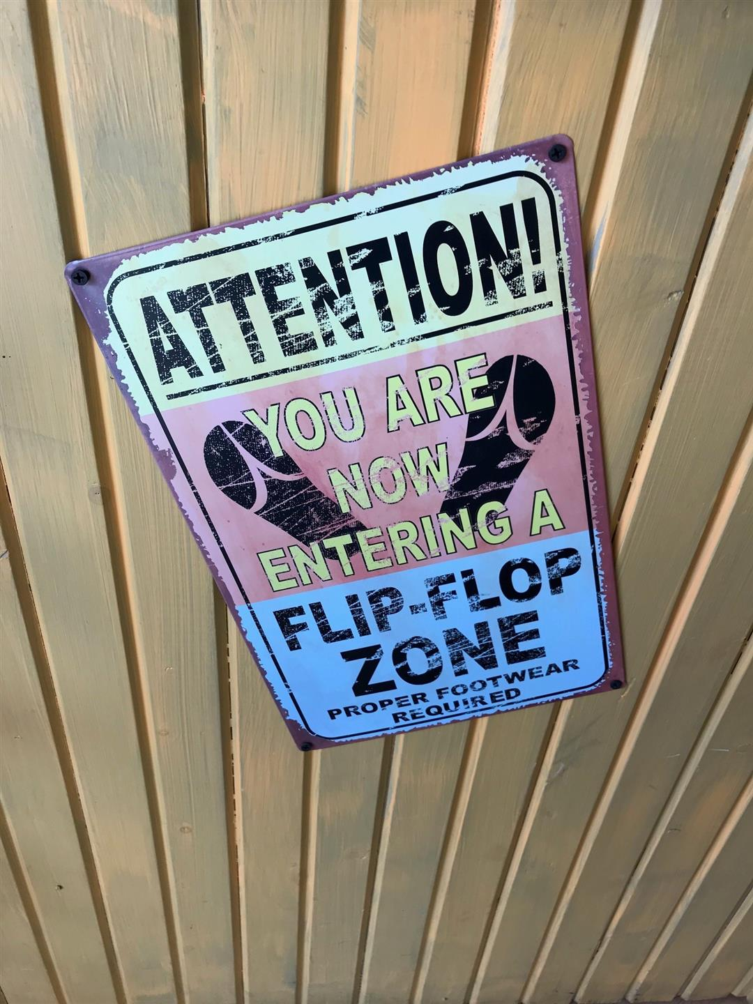 "Wood paneled wall with sign that says ""Attention! You are now entering a flip-flop zone"""