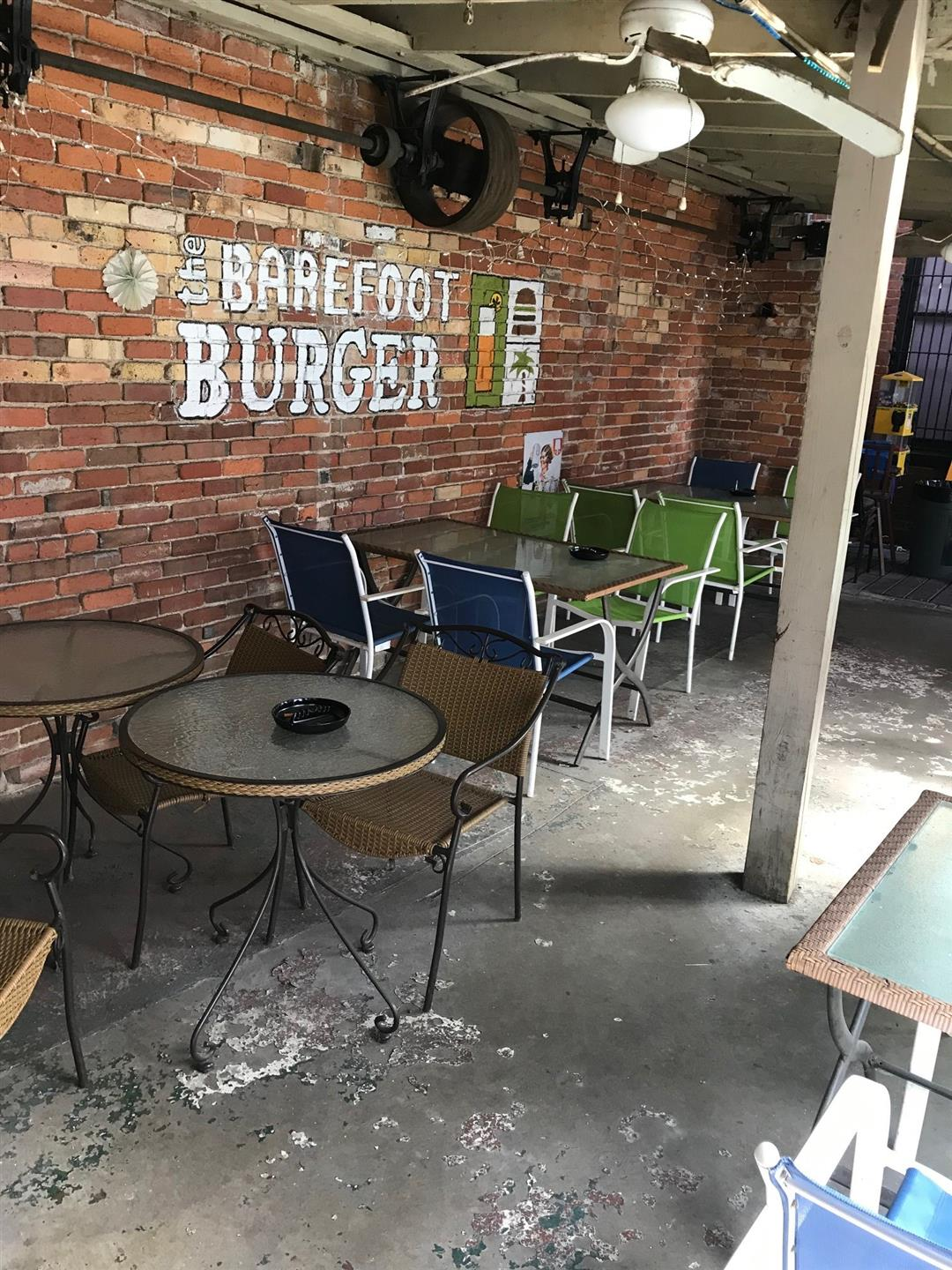 interior view of restaurant with brick wall, and outdoor paio furniture with sign on wall that says Barefoot Burger
