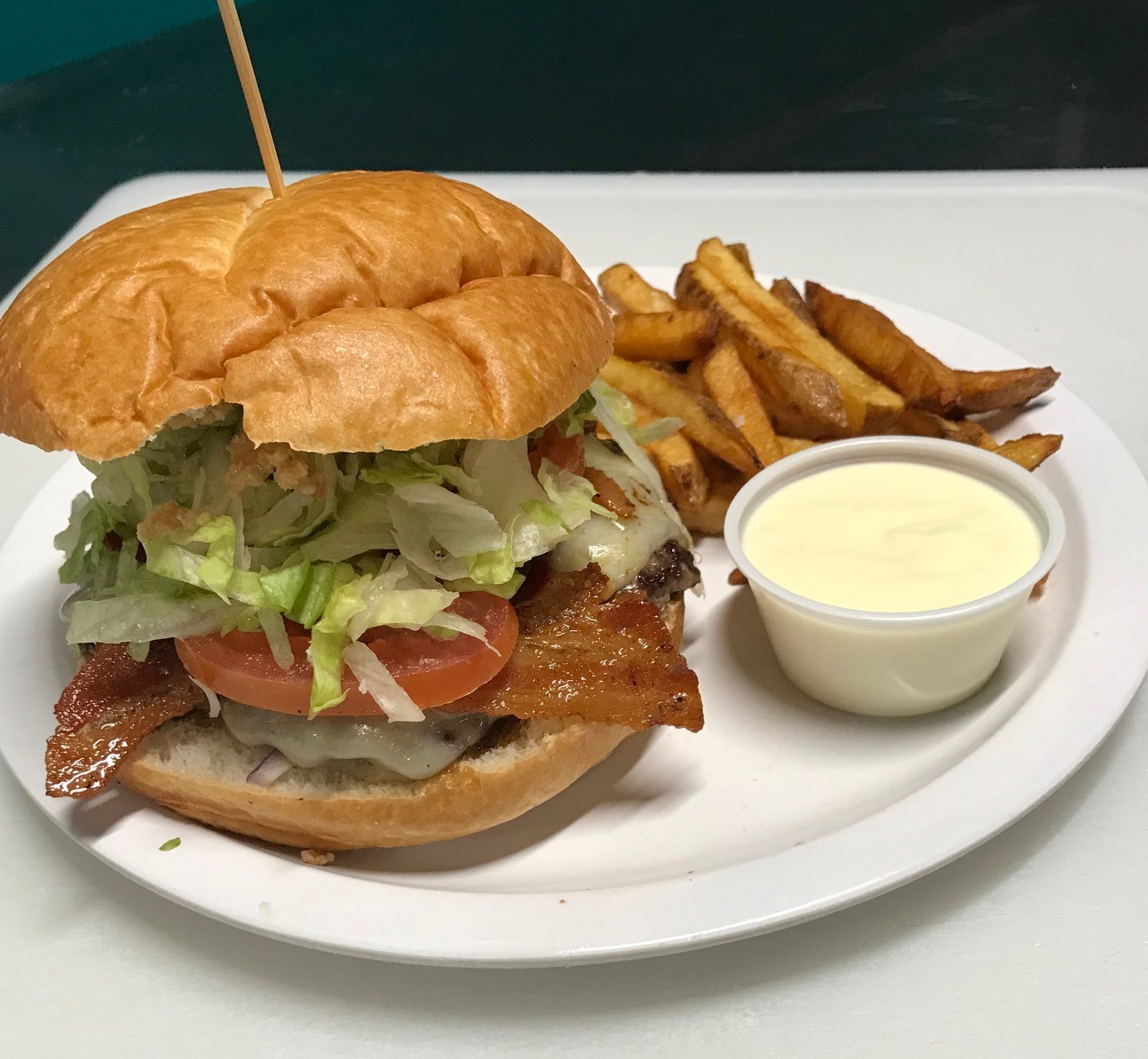 bacon cheeseburger with lettuce, and tomato on plate with side of mayo and french fries