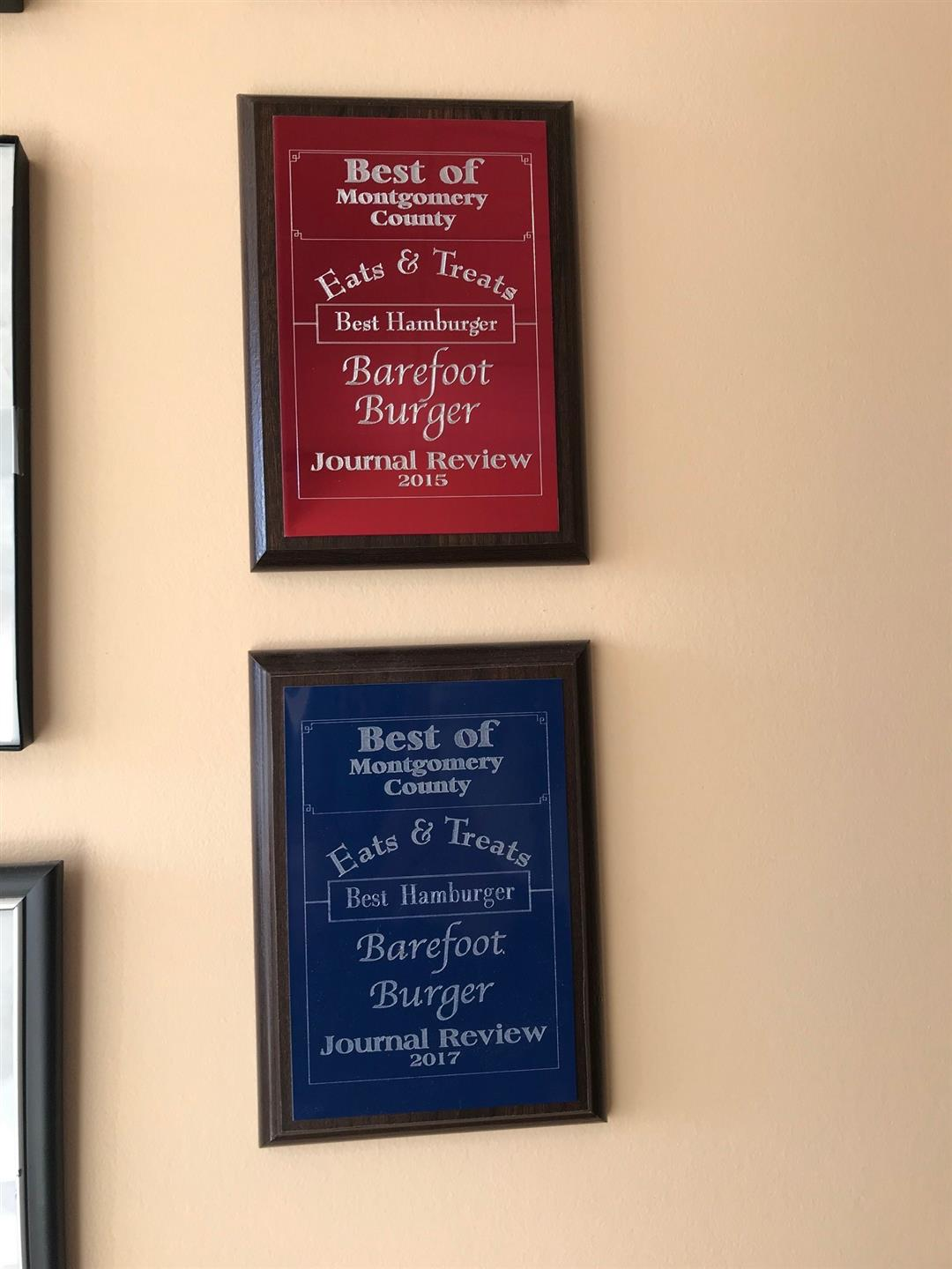 "2 Plaques that read ""Best of montgomery County Eats & Treats: Best Hamburger-Barefoot Burger, Journal Review"" One says 2015 while one says 2017."