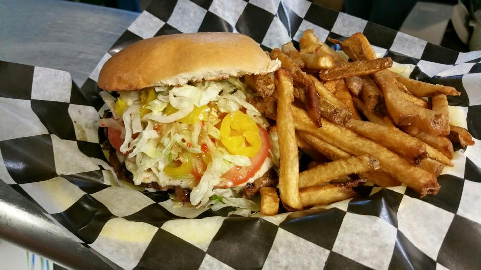 burger with coleslaw, tomato and banana peppers on a bun with a side of fries