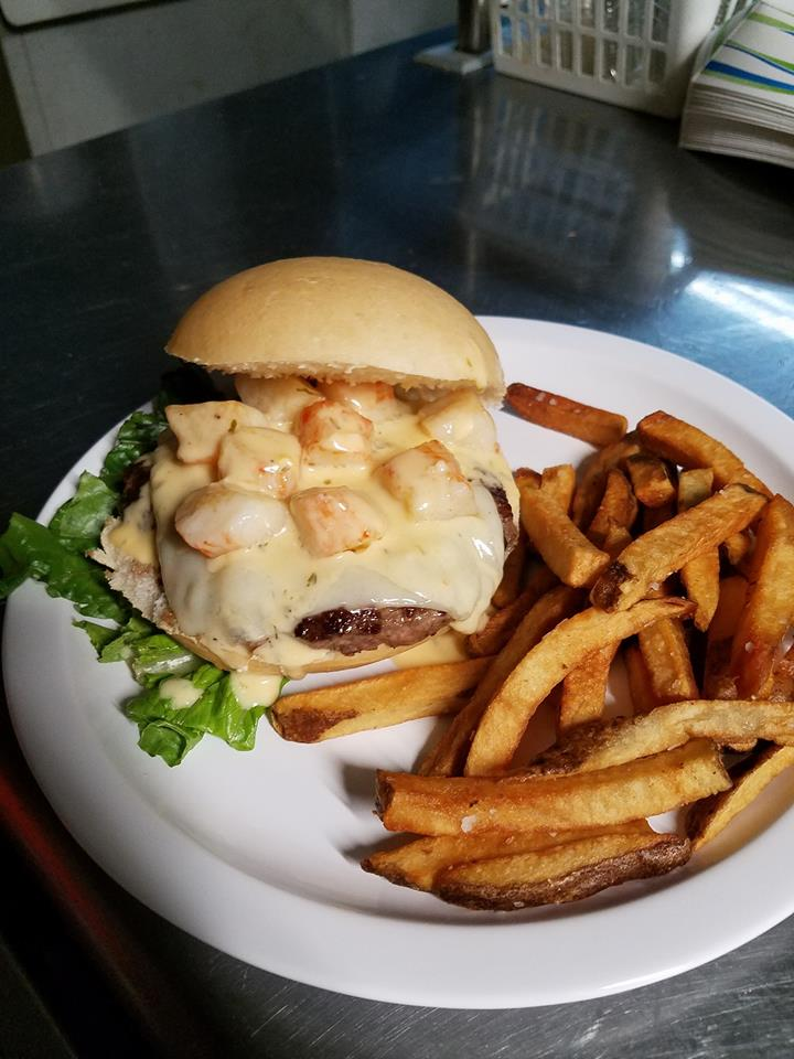 Lobster sauce cheeseburger on a bun with lettuce and a side of fries