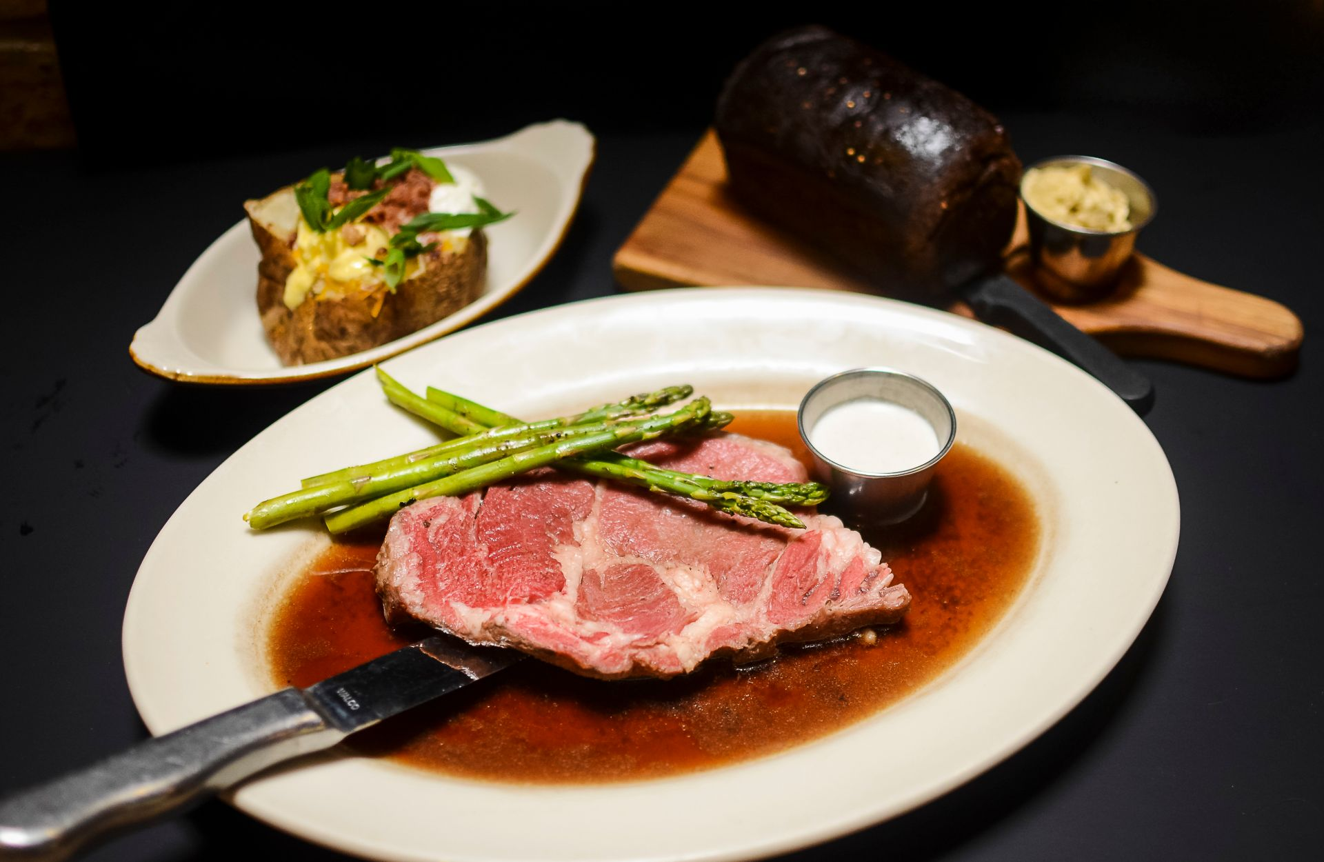 Prime rib on a plate with asparagus and a side of butter, a split baked potato with cheese and bacon and bread with butter