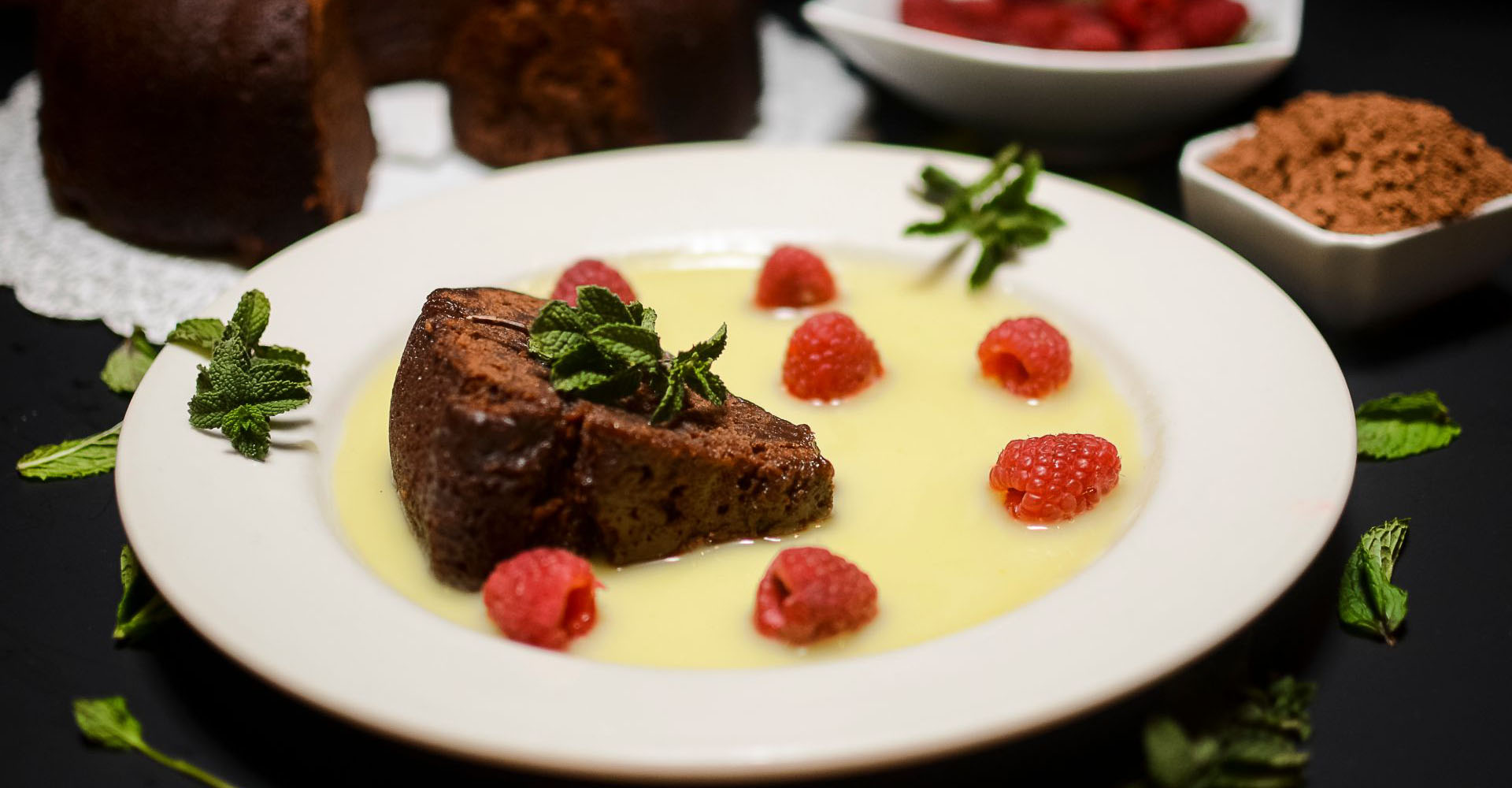 Close-up of a slice of chocolate cake on a plate with a vanilla cream, raspberries and mint leaves
