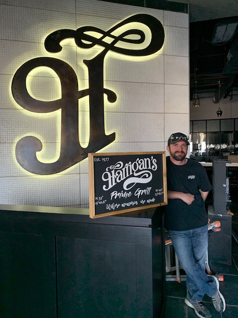 patrick standing in store next to Harrigan's Prime Grill sign