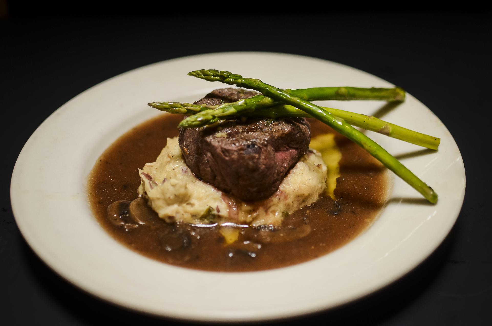 Filet mignon with asparagus and mashed potatoes over a mushroom gravy