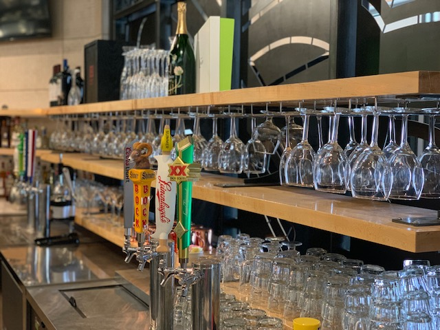 back of the bar with taaps ns glassses on wood shelves