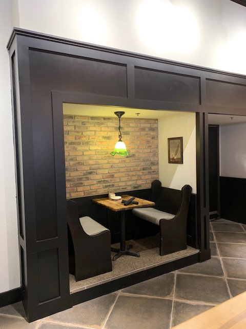 interior view of restaurant with booth table set up in a cutout with warm lighting and brick textured walls