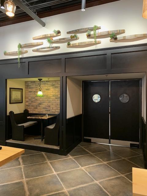 interior shot of dining room booths with a cozy brick texture on wall next to kitchen doors