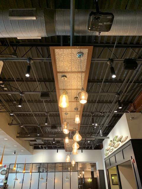 inteior shot of building ceilings with industrial lighting and exposed beams