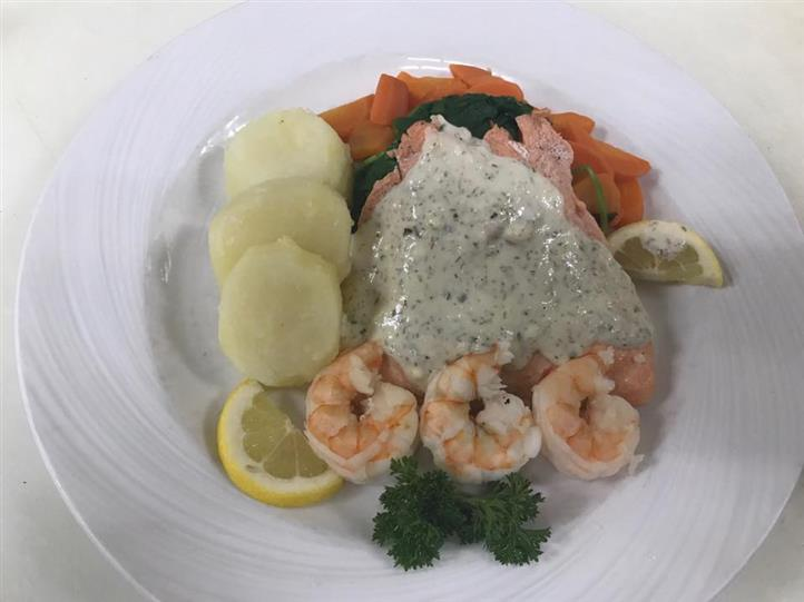 Salmon entree with shrimp, potatoes, carrots and lemon wedges