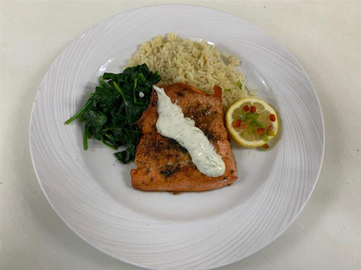 Salmon filet with tartar sauce and a side of sauteed spinach, rice and lemon wedge