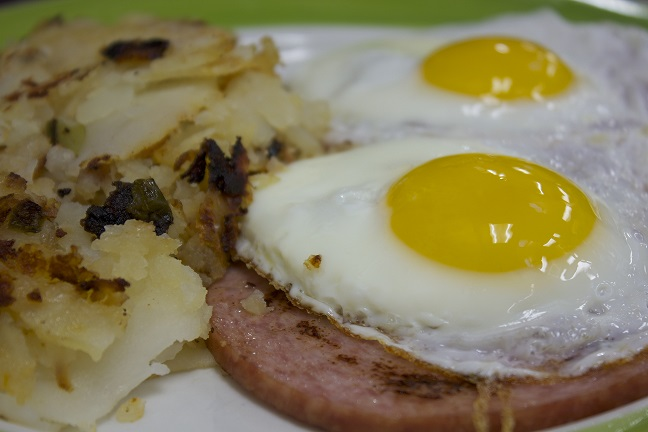 Two eggs sunny side up over Canadian bacon with a side of breakfast potatoes