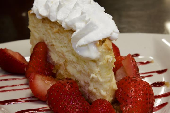 Cheese cake with whipped cream and strawberries