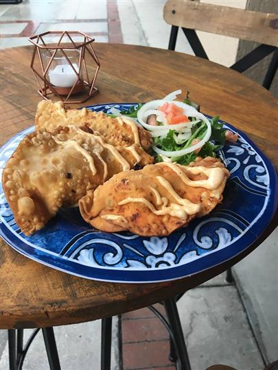 Empanadas on a plate drizzled with spicy sauce and a side of mixed green salad
