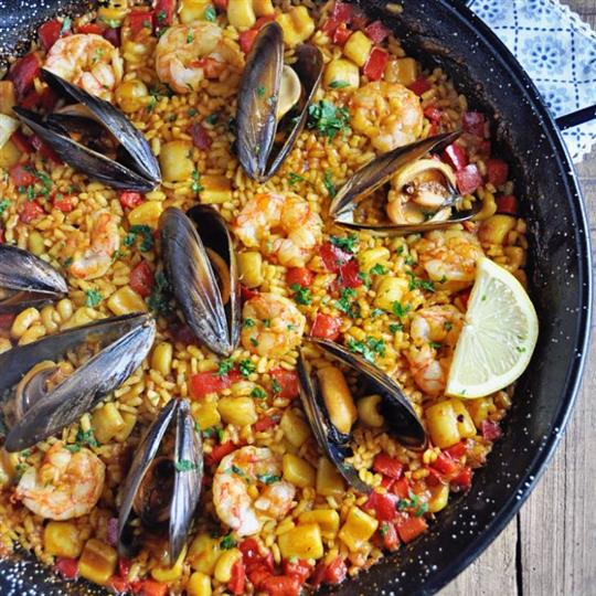 Paella in a large bowl topped with mussels and shrimp