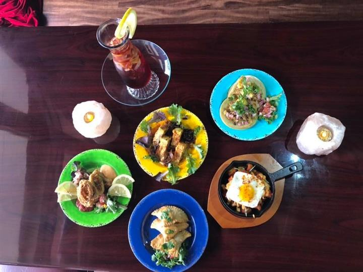 Top-down view of an assortment of entrees on colorful dishes on a wooden table-top with a pitcher of sangria