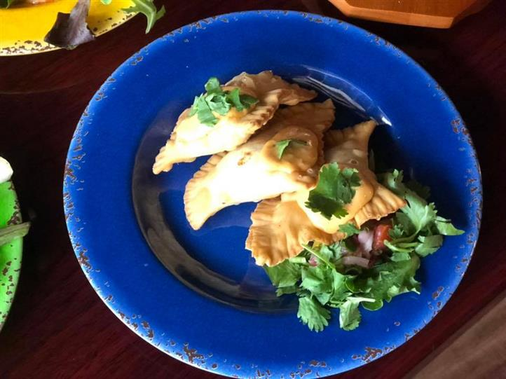 Empenadas topped with cilantro on a plate with a mixed green salad