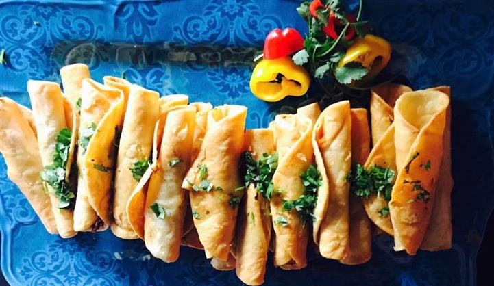 Mini taquitos topped with cilantro on a floral table cloth with sliced banana peppers
