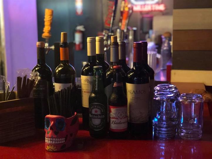 An assortment of bottles of wine and beers on a bar-top