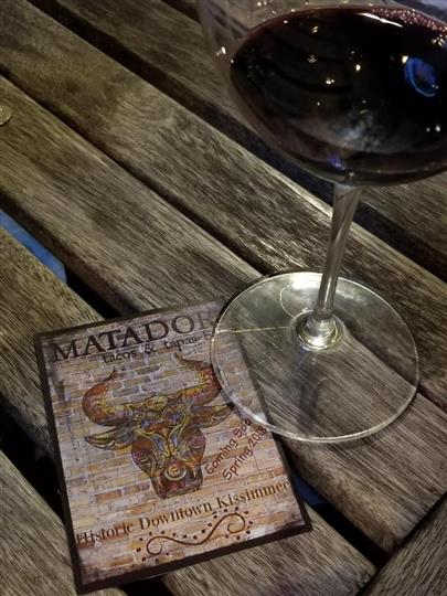 Matador Tacos & Tapas Bar branded drinks coaster with a glass of red wine on a wood table-top