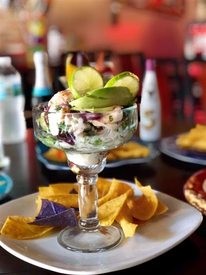 Ceviche in a tall glass with sliced limes and tortilla chips