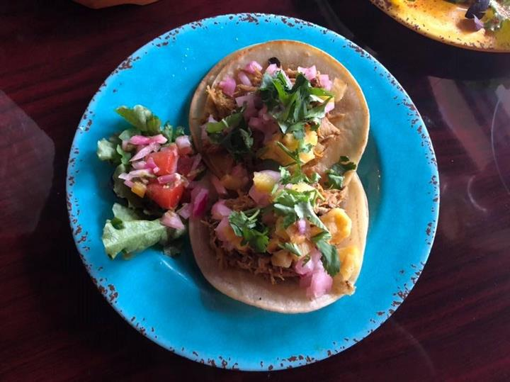 Chicken tacos on a plate with pickled red onions, mango and cilantro on corn tortillas