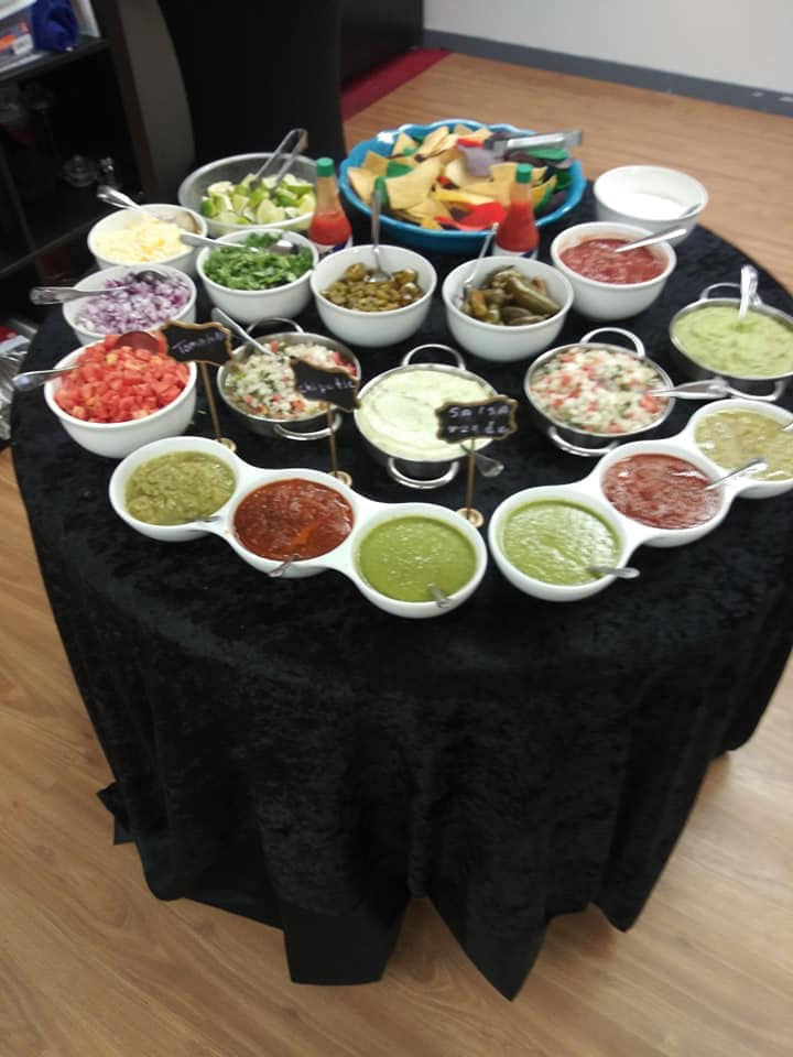 catering display with all the sides and extras to make a taco and nachos. Different sauces, cheese, onions, jalapenos, tomatoes, lettuce and chips.