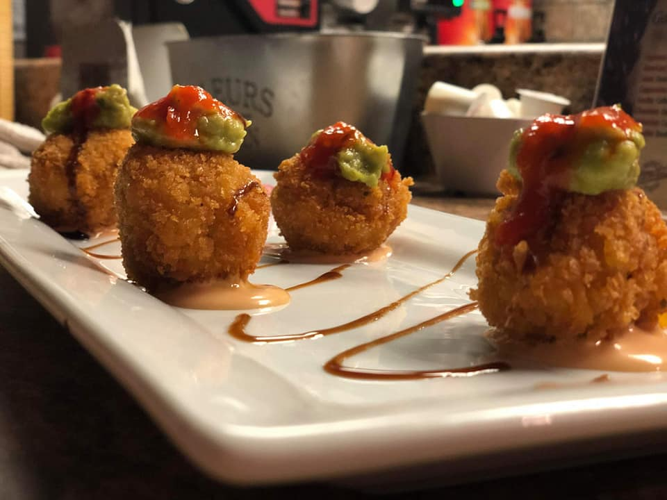 side shot of a menu item with four fried balls with a guacamole dallop and salsa on top on a white plate