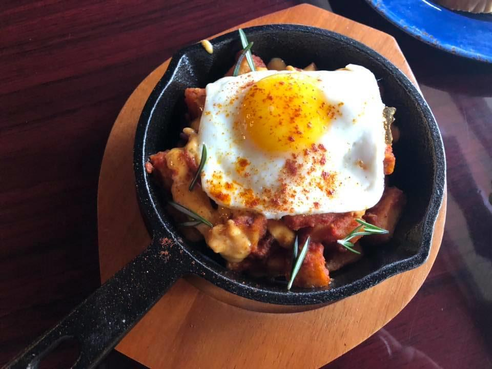breakfast menu item with an easy over egg on top and seasoning in a cast iron pot