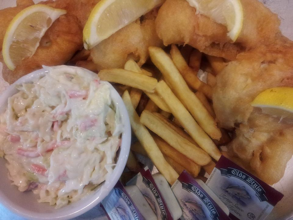 Fish and chips platter with lemon wedges and coleslaw