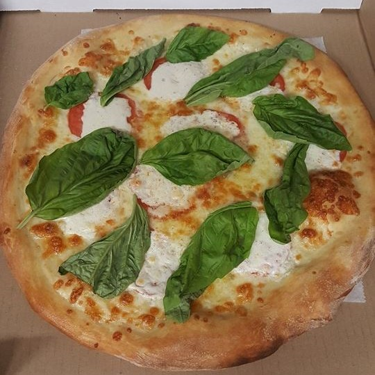 small size pizza topped with ricotta cheese, sliced tomatoes and basil leaves.