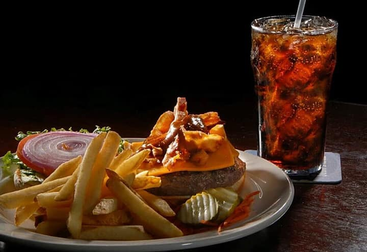Bacon cheese burger on a plate with pickles, red onion, tomatoes and lettuce with fries and a soda in a glass with ice