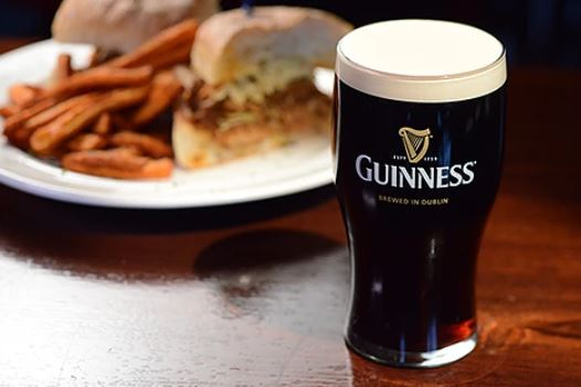 Guinness beer on a wood table-top with a sandiwch on a plate with fries