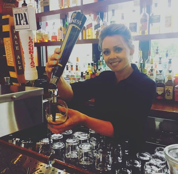 Bartender smiling pouring a beer from a beer tap