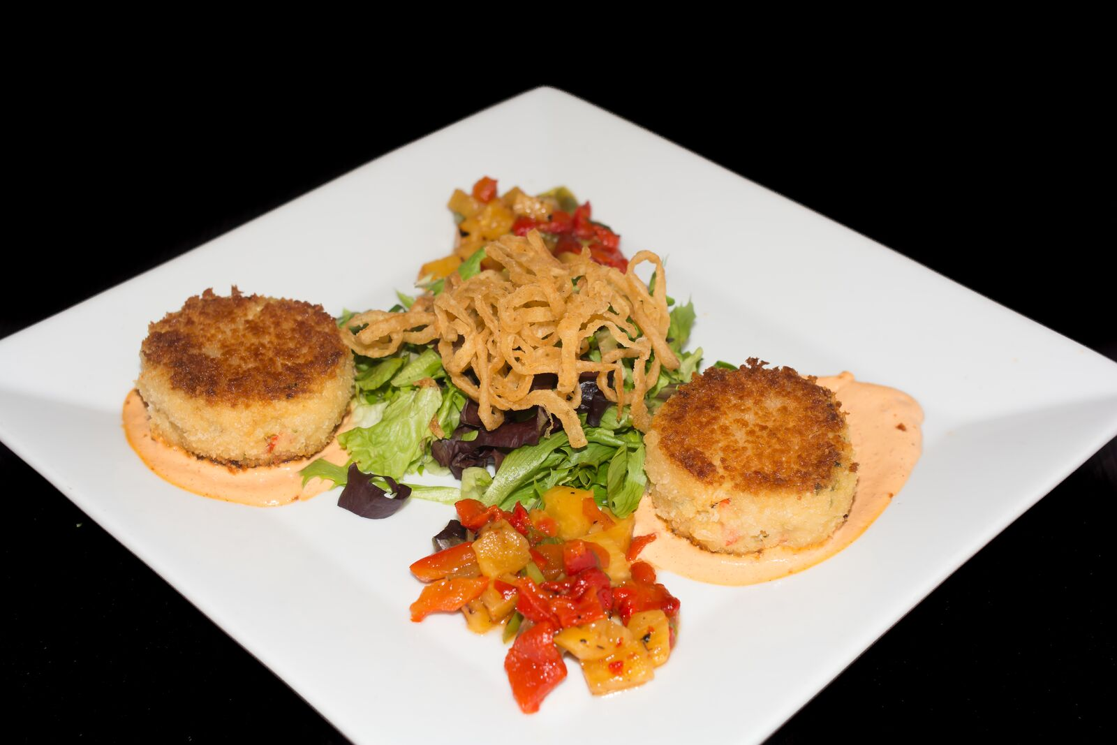 crab cakes with a salad in the middle with wonton strips