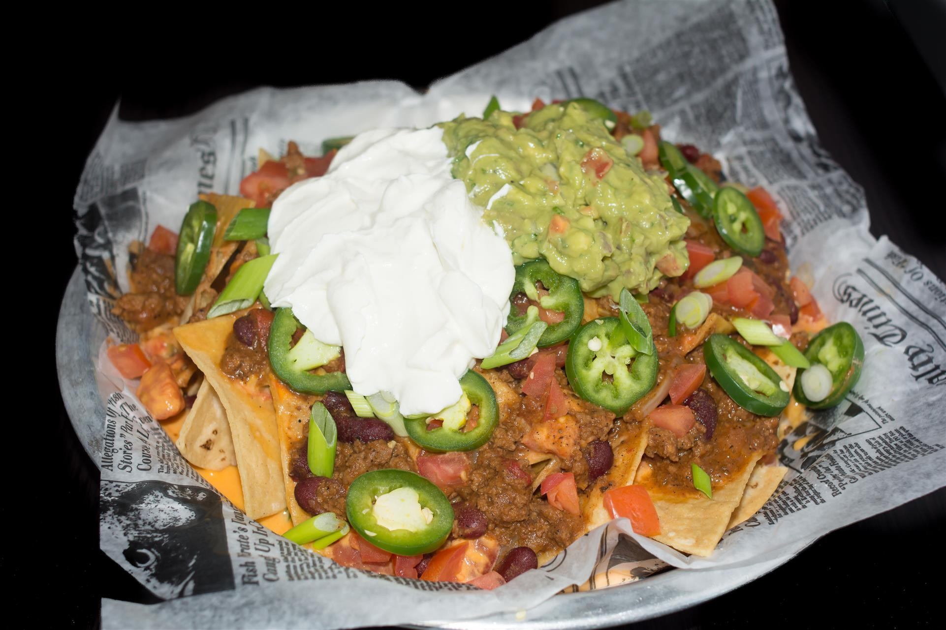 nachos Fresh nachos layered with our homemade chili cheese sauce, topped with fresh sliced jalapeños, chopped tomatoes, guacamole and sour cream.