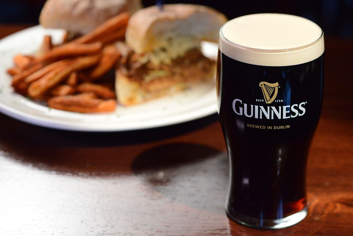 guinness with a sandwich and fries