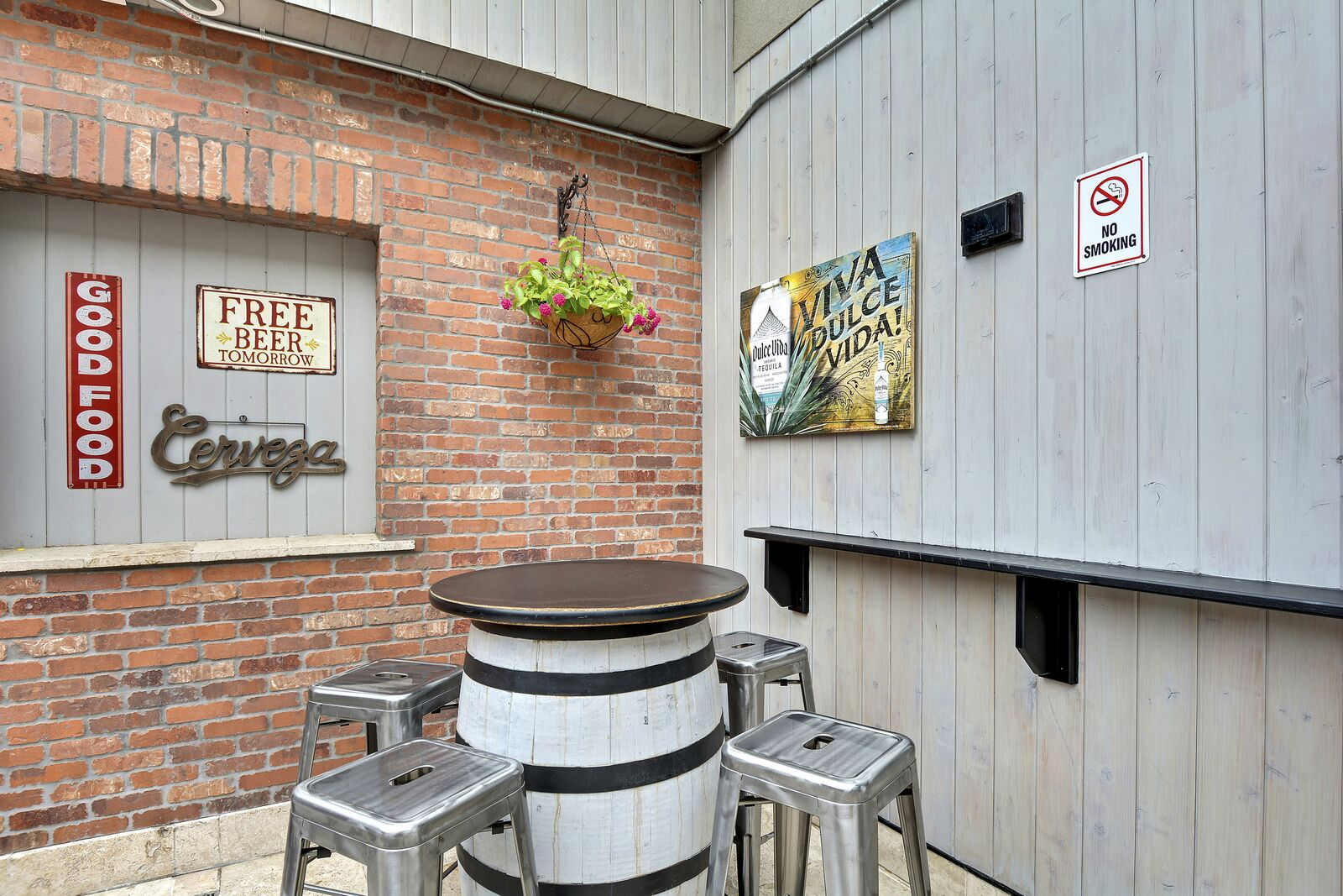 outdoor view of a barrell table with stools and signs on the walls