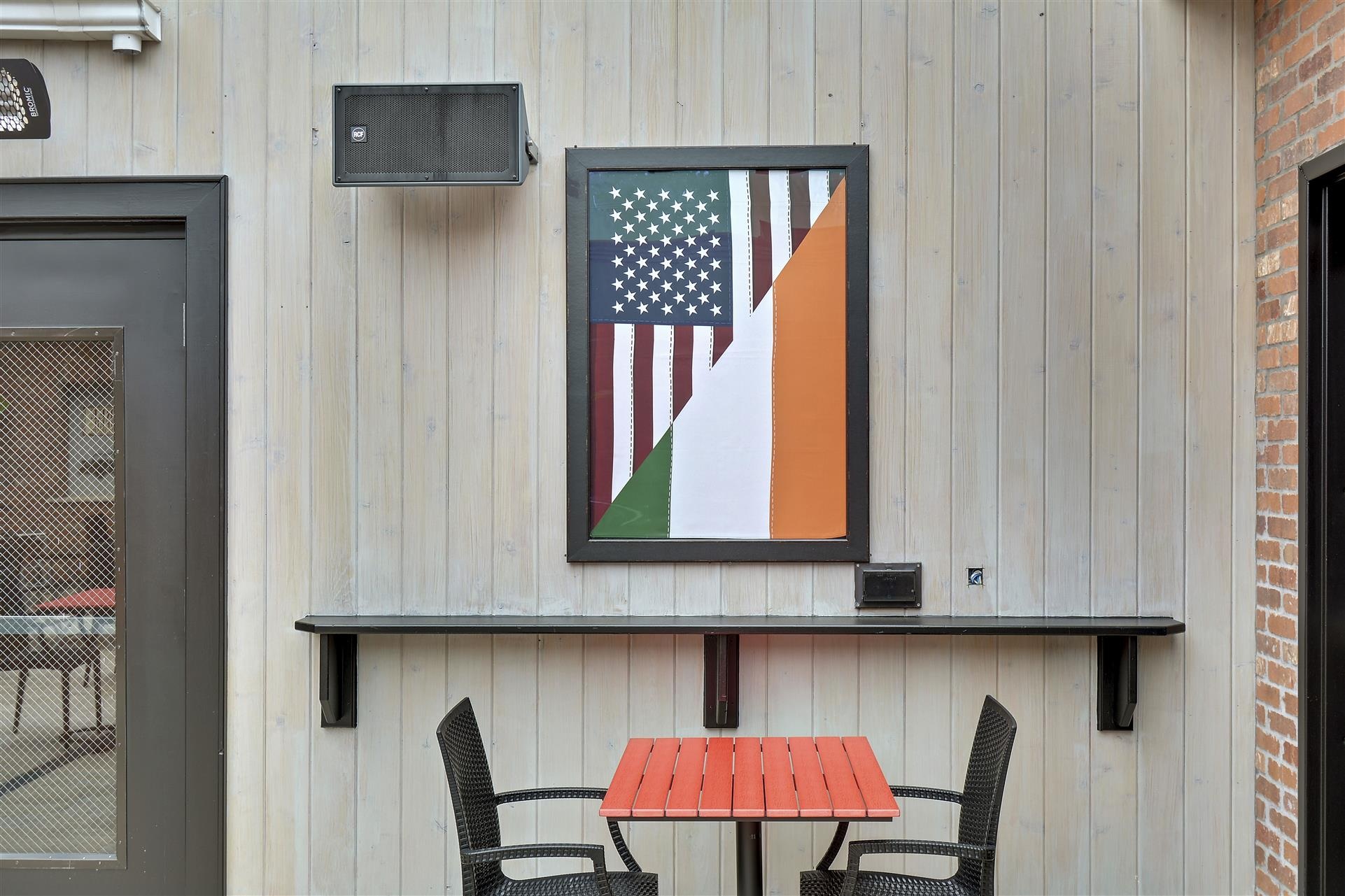 outdoor view of a flag on the wall behind a table and chairs