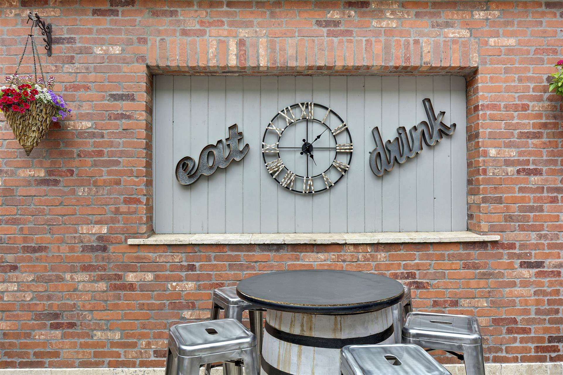 outdoor view of eat drink signs on the wall behind a barrell table with stools