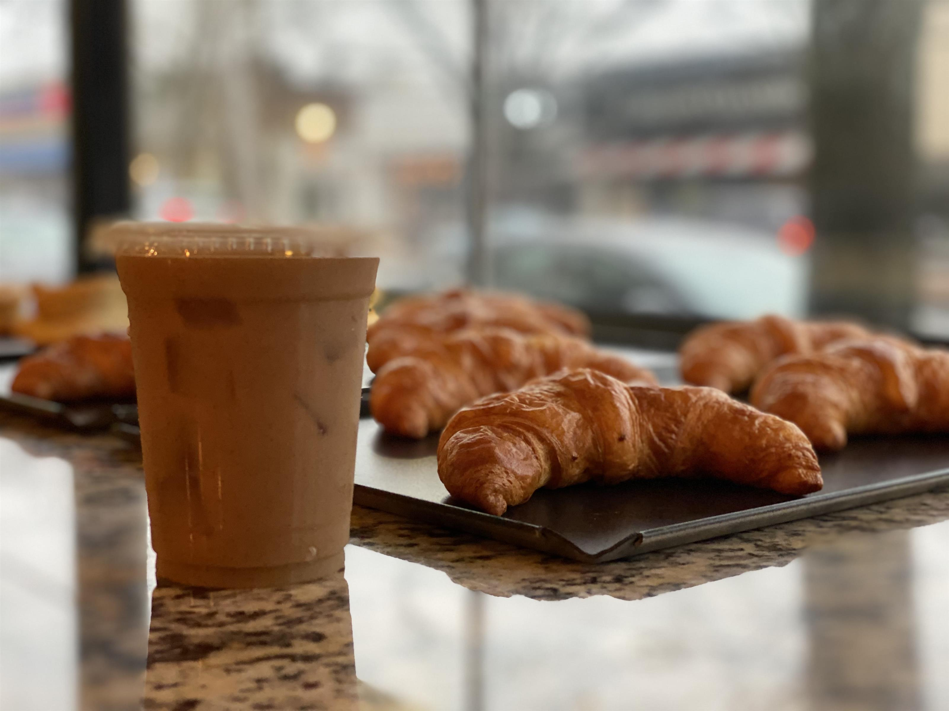 cup of iced coffee on a counter next to a tray of baked croissants